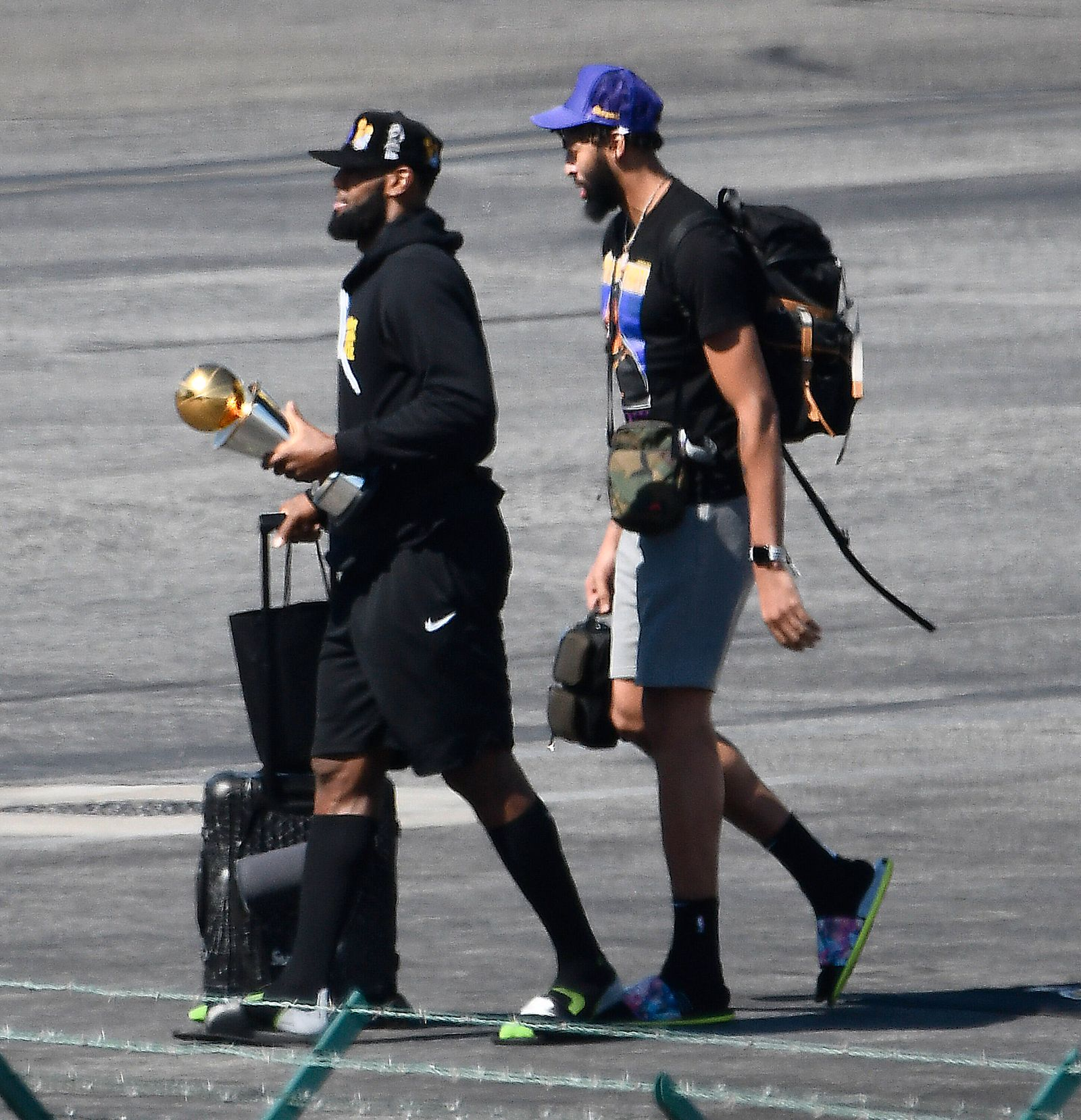 Los Angeles Laker LaBron James walks off with the winning trophy in hand as the Lakers return home for winning the NBA,