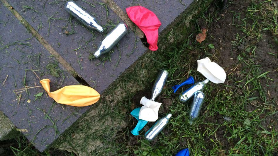 Party-Relikte in einem Park: Lachgas-Kartuschen und Luftballons