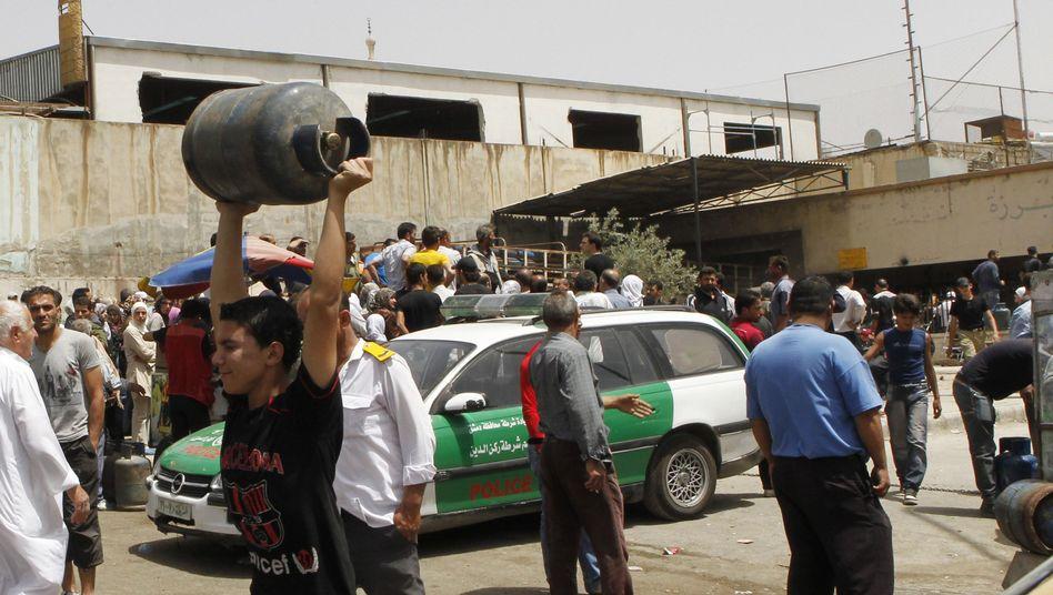 Syrer mit Gasflasche: Die Bevölkerung leidet, die Wirtschaftselite verdient dazu