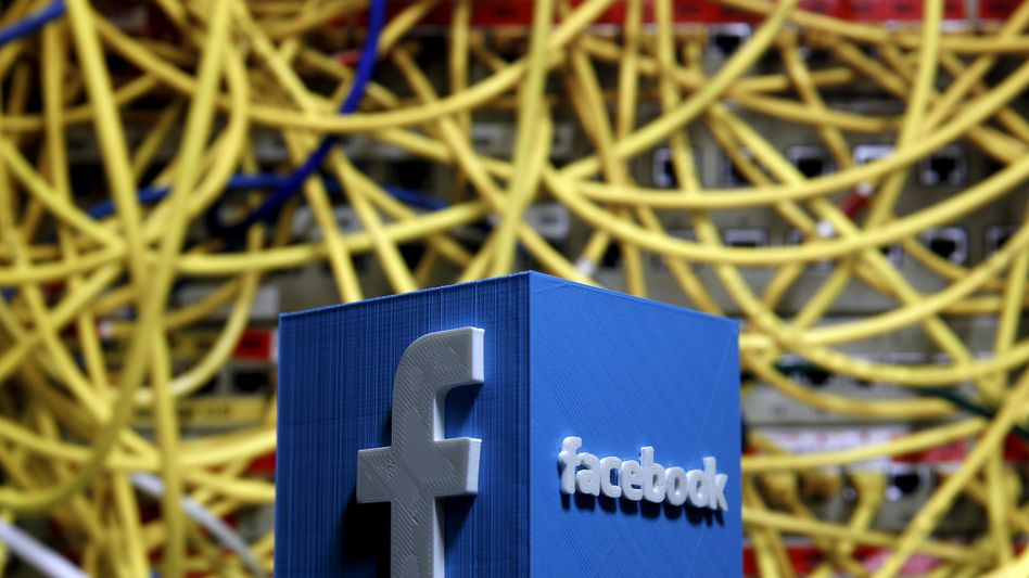 Facebook-Logo aus einem 3D-Drucker vor Netzwerkkabeln