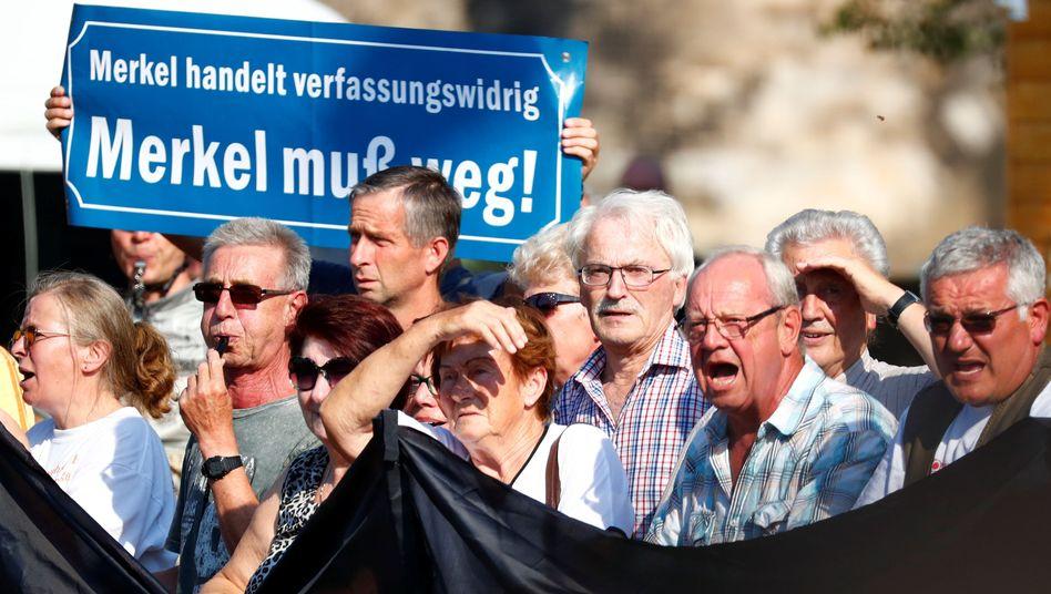 "An anti-Merkel protest in Dresden last August. ""Merkel must go!"" reads the sign."