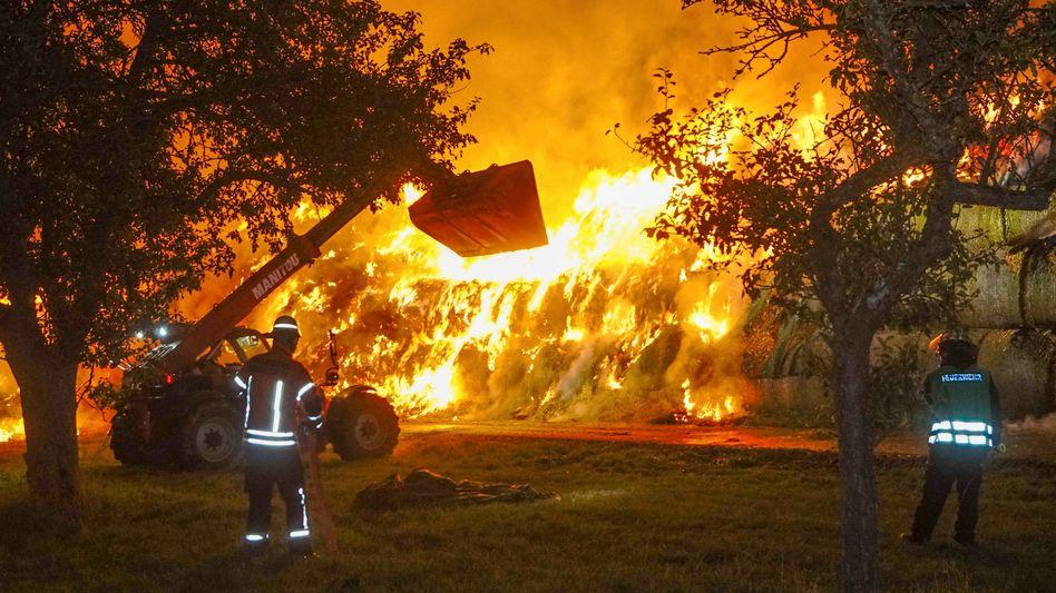 Einsatzkräfte der Feuerwehr löschen einen Brand von rund 400 Strohballen (Archiv)