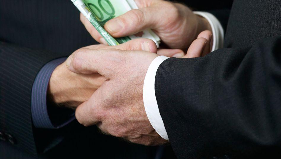 Geldübergabe (Archivbild): Schattenwirtschaft wächst rasant