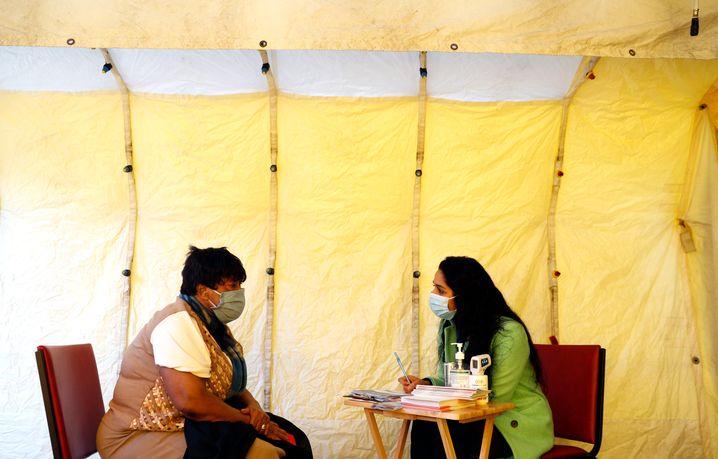 Eine freiwillige Helferin (r.) berät eine Patientin vor der Impfung
