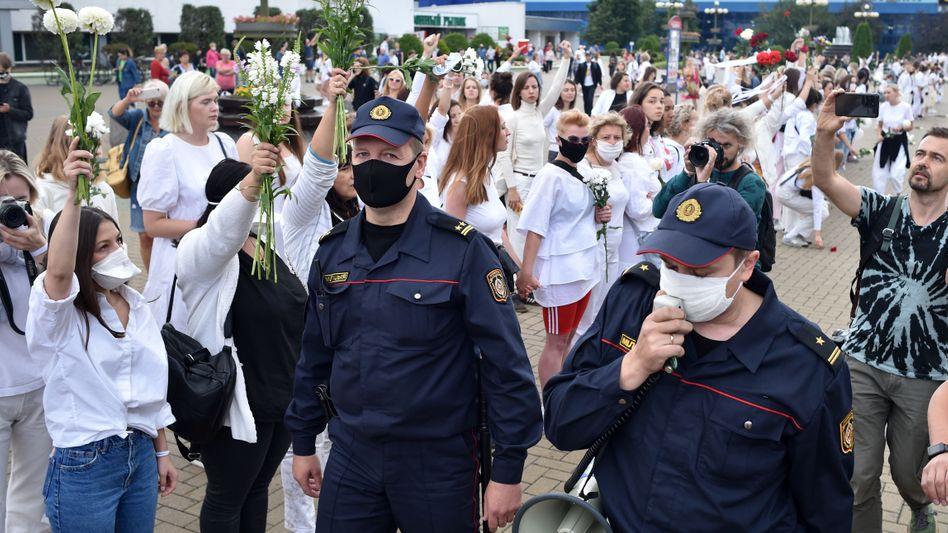 Vor dem Minsker Markt versammeln sich Hunderte Frauen in Weiß mit Blumen