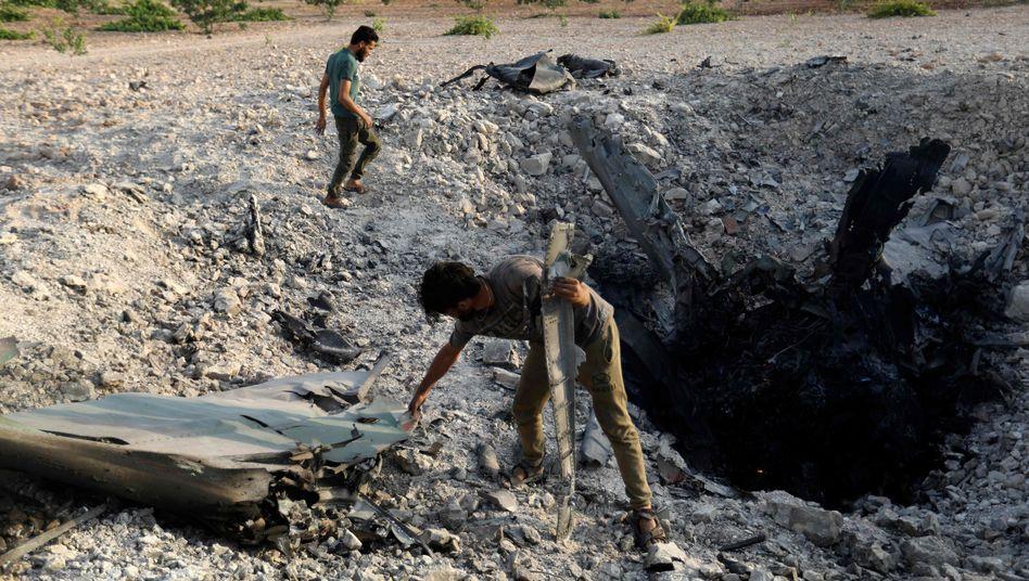 Rebellen stehen bei den Trümmern des abgestürzten Flugzeugs