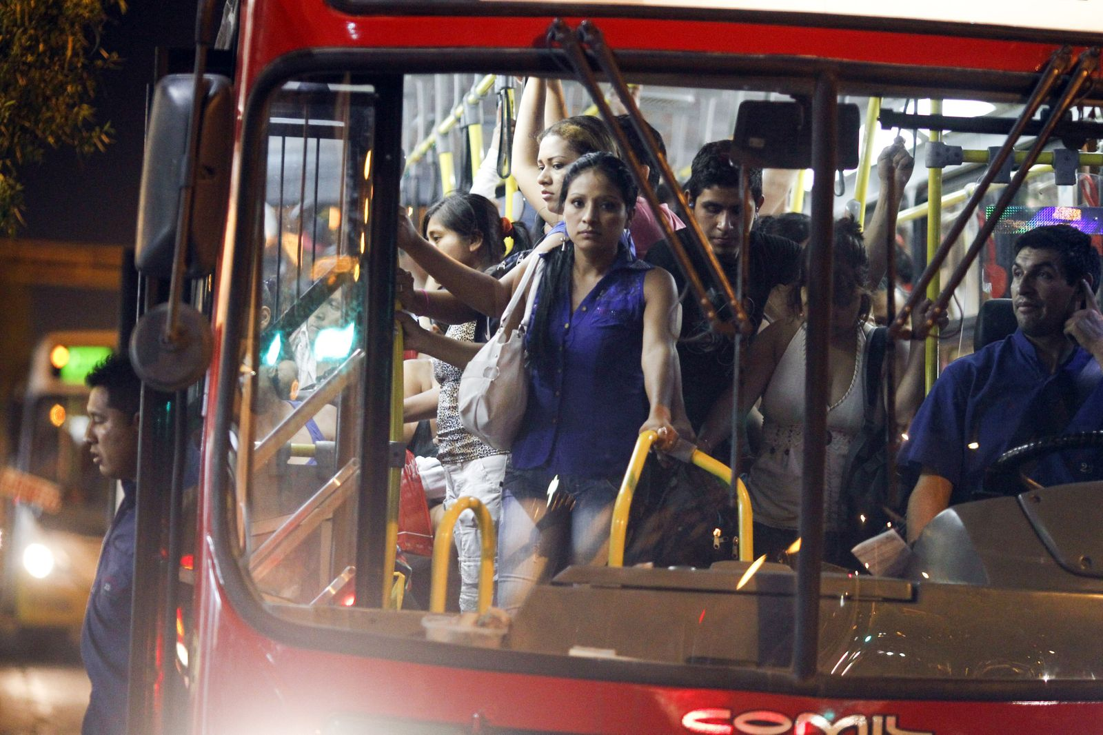 Passengers stand in a packed public bus in downtown Lima