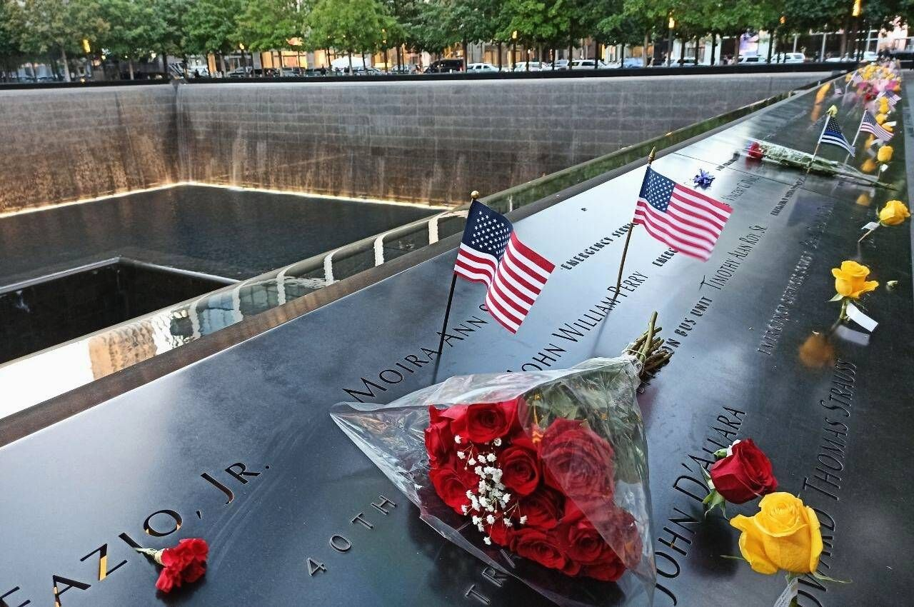 US 9/11 Anniversary 6648569 11.09.2021 Flags and flowers are placed on the 9/11 Memorial on the 20th anniversary of the
