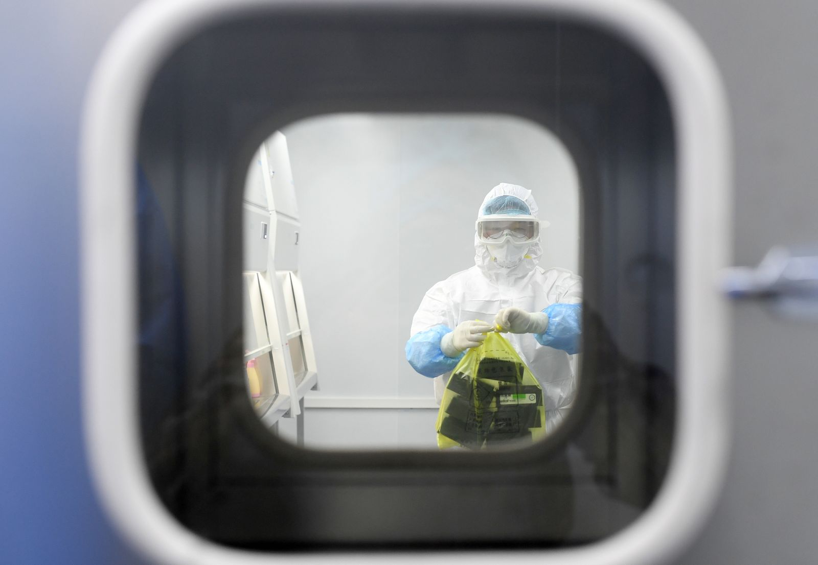 Worker in protective suit examines specimens inside a laboratory following an outbreak of the novel coronavirus in Wuhan