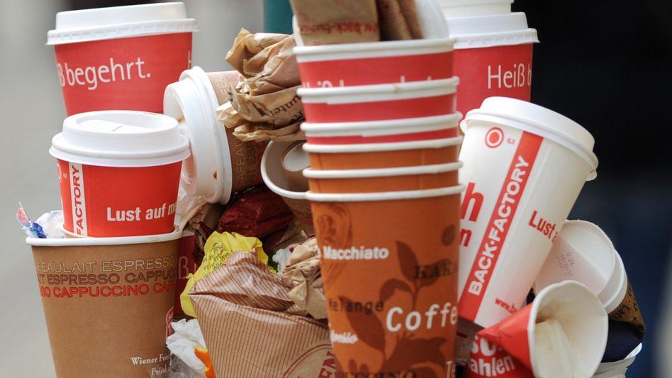 Einwegkaffeebecher in einem vollen Mülleimer