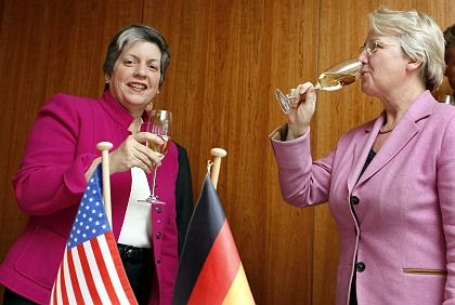 Janet Napolitano (left) and Annette Schavan celebrate with a glass of sparkling wine after signing the treaty Monday.