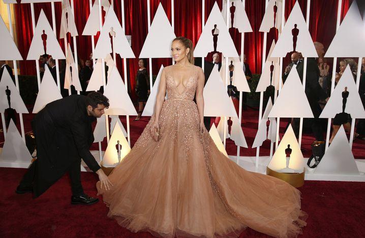 Der Assistenz zupft noch schnell die Robe zurecht: So viel Hilfe kann Jennifer Lopez aber auch bei einem derart ausufernden Kleid erwarten