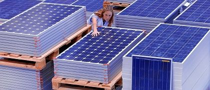 The German economy is recovering and unemployment is down. Here an employee checks solar panels in a Wismar plant.
