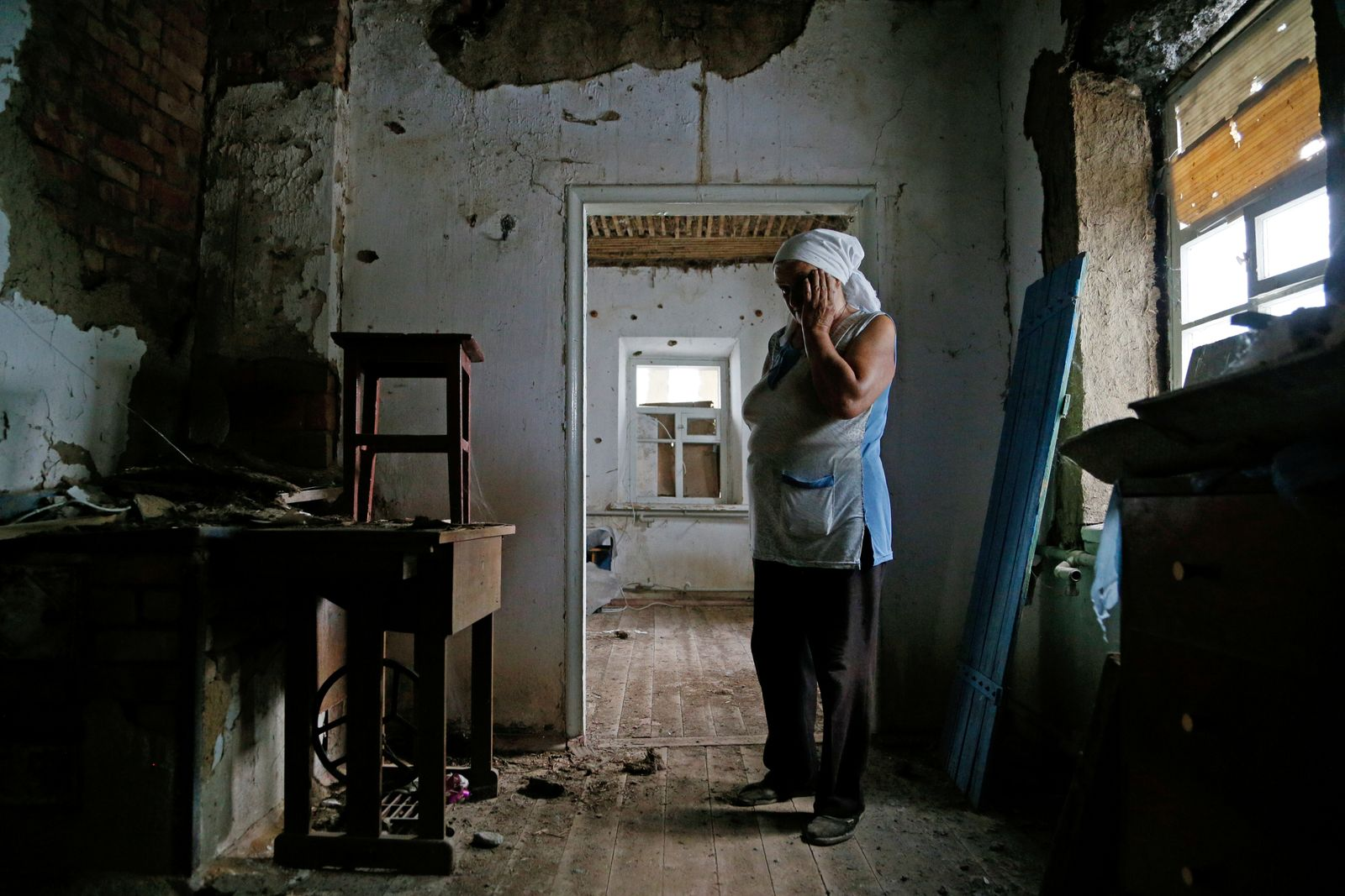 Local resident Katerina Izvekova shows her house damaged during a military conflict in Vesele