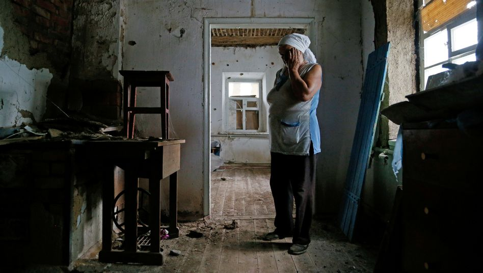 Eine Frau zeigt ihr zerstörtes Haus in einem Dorf nahe Donetsk