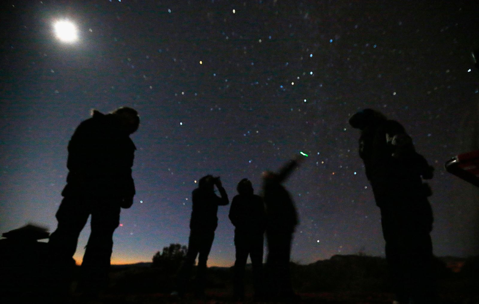 People look at the night sky using night vision goggles during an UFO tour in desert outside Sedona