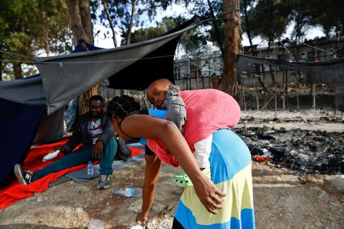 Eine Frau trägt ihr Baby vor einem abgebrannten Zelt im Flüchtlingslager Moria