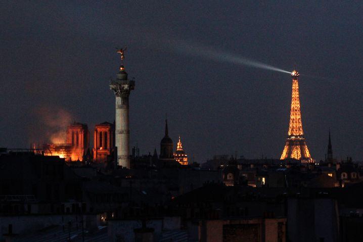 15.04.2019, Frankreich, Paris: Feuerschein erhellt die Pariser Kathedrale Notre-Dame (l). In der weltberühmten Kathedrale Notre-Dame in Paris war am Montagabend ein Feuer ausgebrochen. Über dem Wahrzeichen waren Flammen und eine riesige Rauchsäule zu sehen. Ein kleiner Spitzturm in der Mitte des Daches stürzte ein. Foto: Matthias Wagner/dpa +++ dpa-Bildfunk +++ | Verwendung weltweit