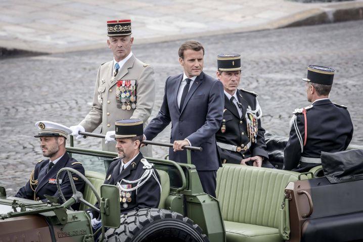 """Präsident Emmanuel Macron (Mitte) während des französischen Nationalfeiertags: Die Regierung habe Hinweise, dass sich die Ausbreitung des Virus """"ein wenig beschleunigt"""""""