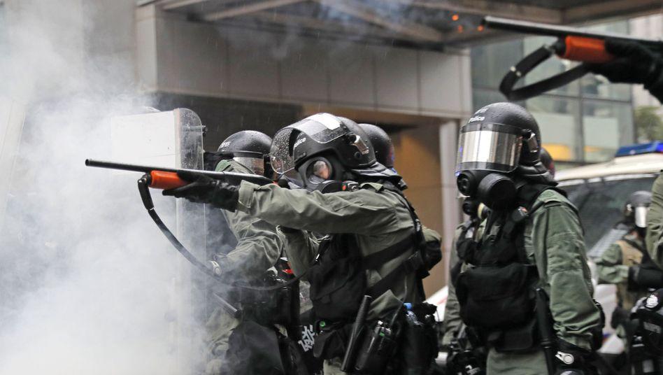 Polizisten zielen mit ihren Waffen während eines Protests: Tränengas und ein scharfer Schuss