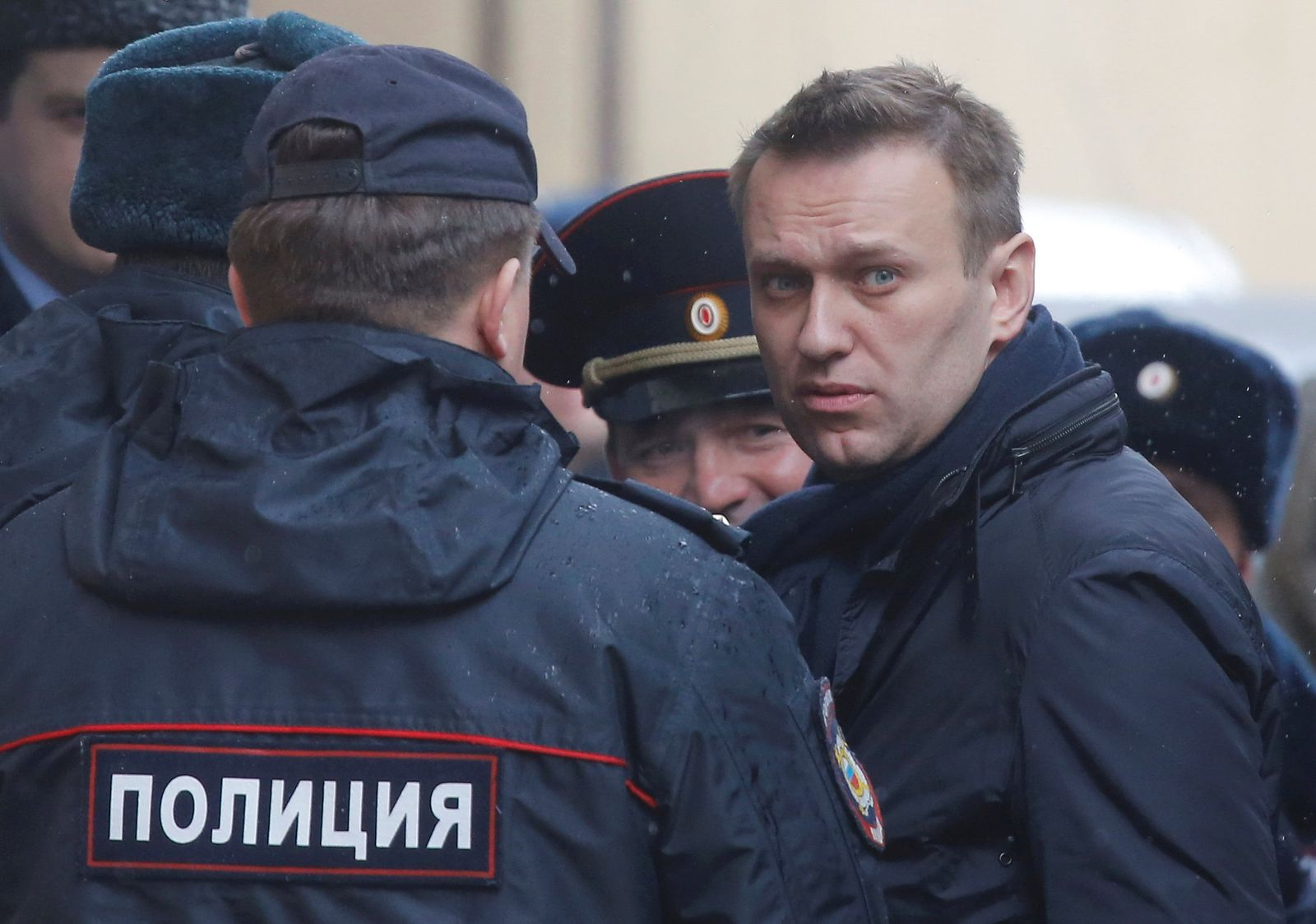 Russian opposition leader Navalny is escorted upon his arrival for hearing after being detained at protest against corruption and demanding resignation of PM Medvedev, at Tverskoi court in Moscow