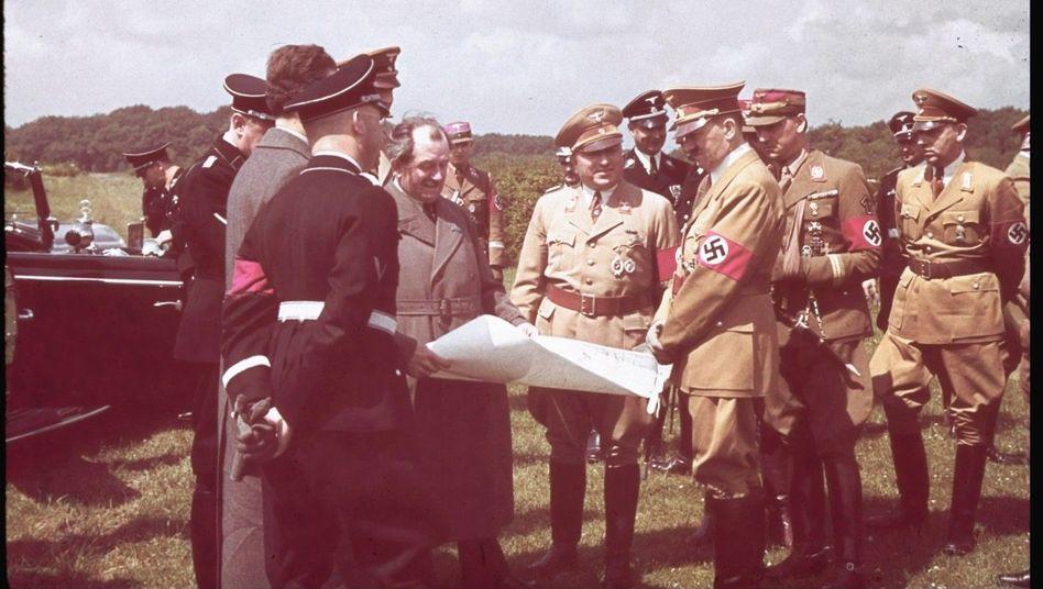 Adolf Hitler und der Autokonstrukteur Ferdinand Porsche (ohne Kappe) 1938bei der Grundsteinlegung des Volkswagenwerks Fallersleben, heute Wolfsburg