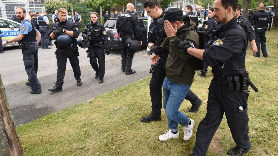 Polizeibeamte führen einen jungen Mann ab, der sich zuvor mit etwa 40 anderen Demonstranten an einer Protestkundgebung in Darmstadt beteiligt hatte.
