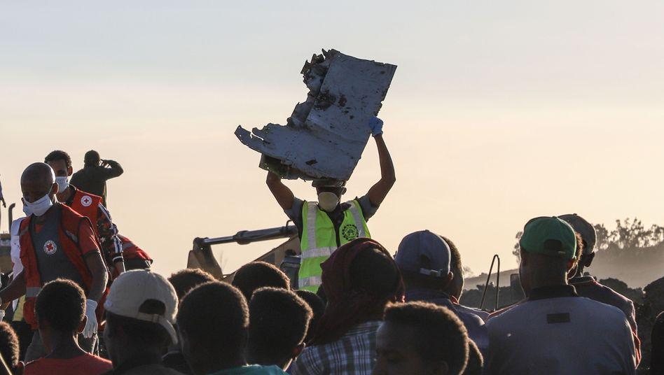 Ein Mann trägt ein Wrackteil der abgestürzten Maschine