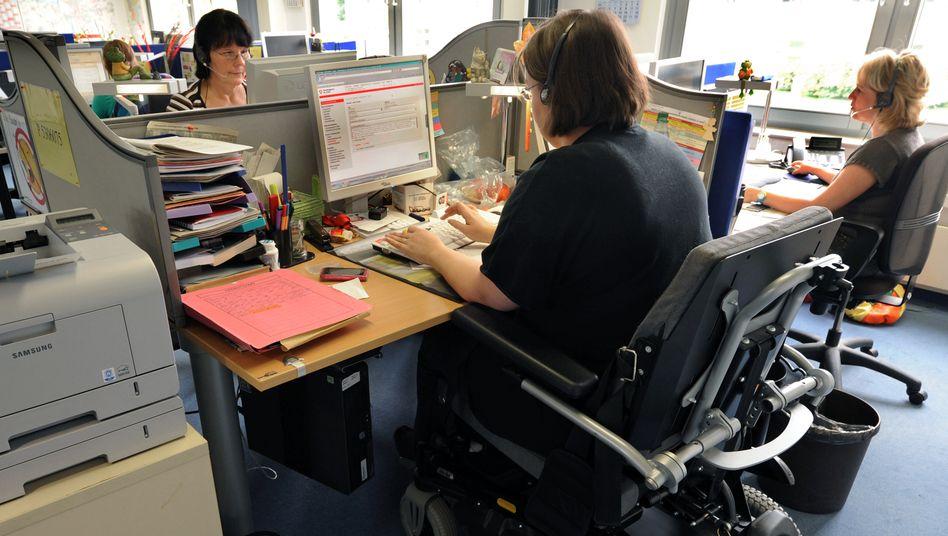 Eine Frau im Rollstuhl arbeitet in einem Servicecenter (Archivbild): Größere Betriebe ohne Behinderte müssen Hunderte Euro zahlen