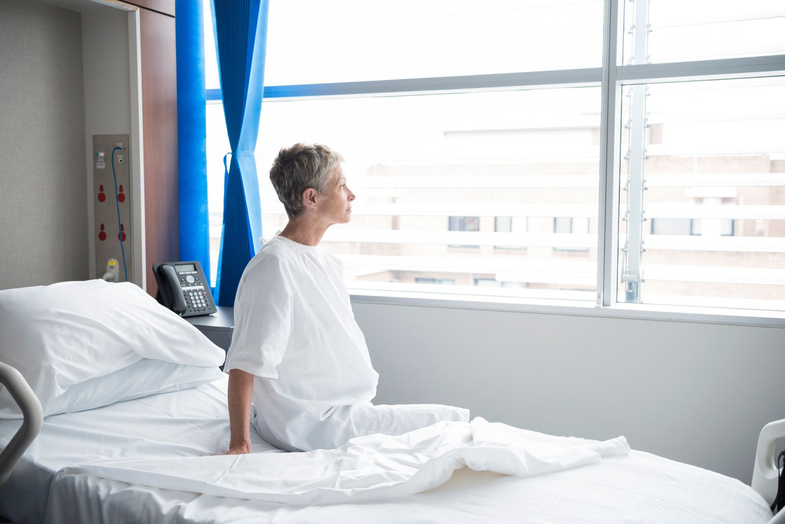 Senior woman sitting on hospital bed looking out of window