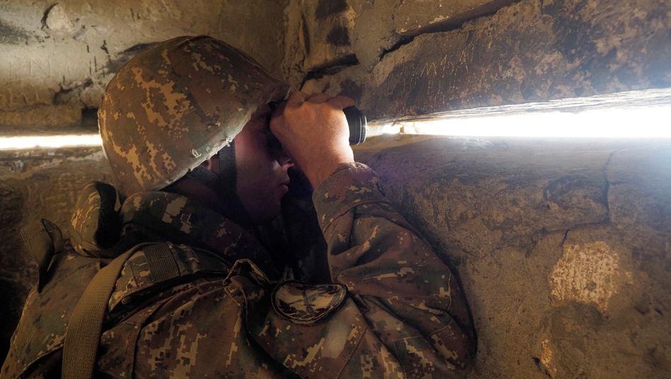 Ein armenischer Soldat beobachtet von einem Unterschlupf in Stepanakert aus die aserbaidschanischen Stellungen