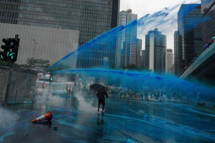Polizisten richten blau gefärbte Wasserstrahlen auf Demonstranten