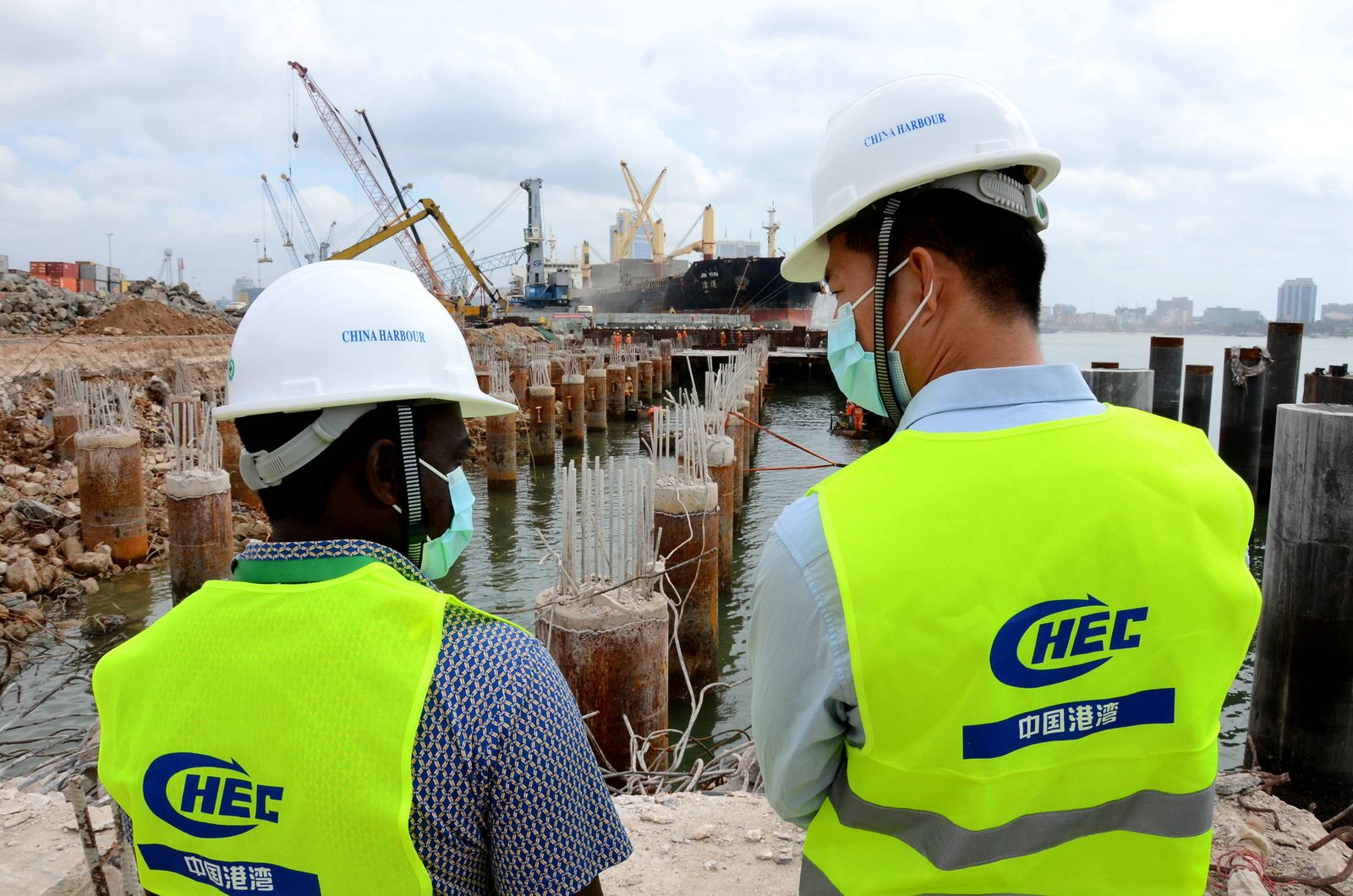 (200714) -- DAR ES SALAAM, July 14, 2020 (Xinhua) -- Engineers from China and Tanzania talk about the construction schem