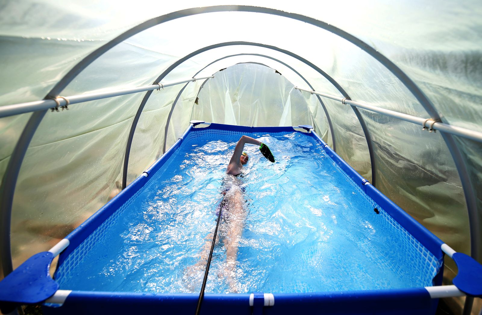 Iman Avdic maintains her form by practicing in a small plastic pool inside an improvised greenhouse in her grandfather's orchard in Doboj