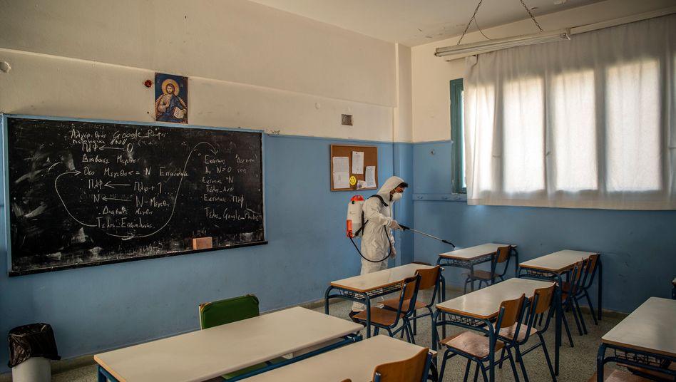 Ein städtischer Angestellte in Schutzausrüstung desinfiziert eine Schule in Athen
