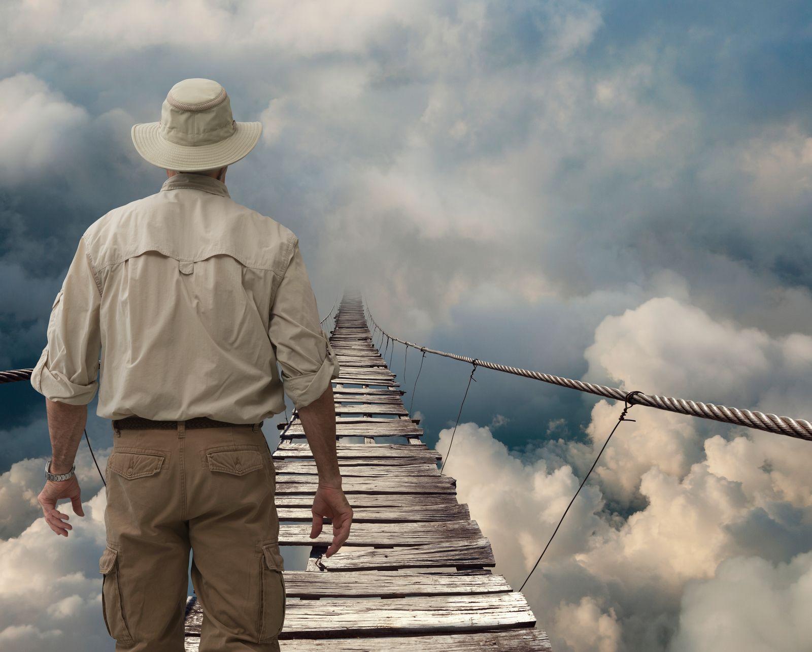 Caucasian explorer examining wooden rope bridge in clouds