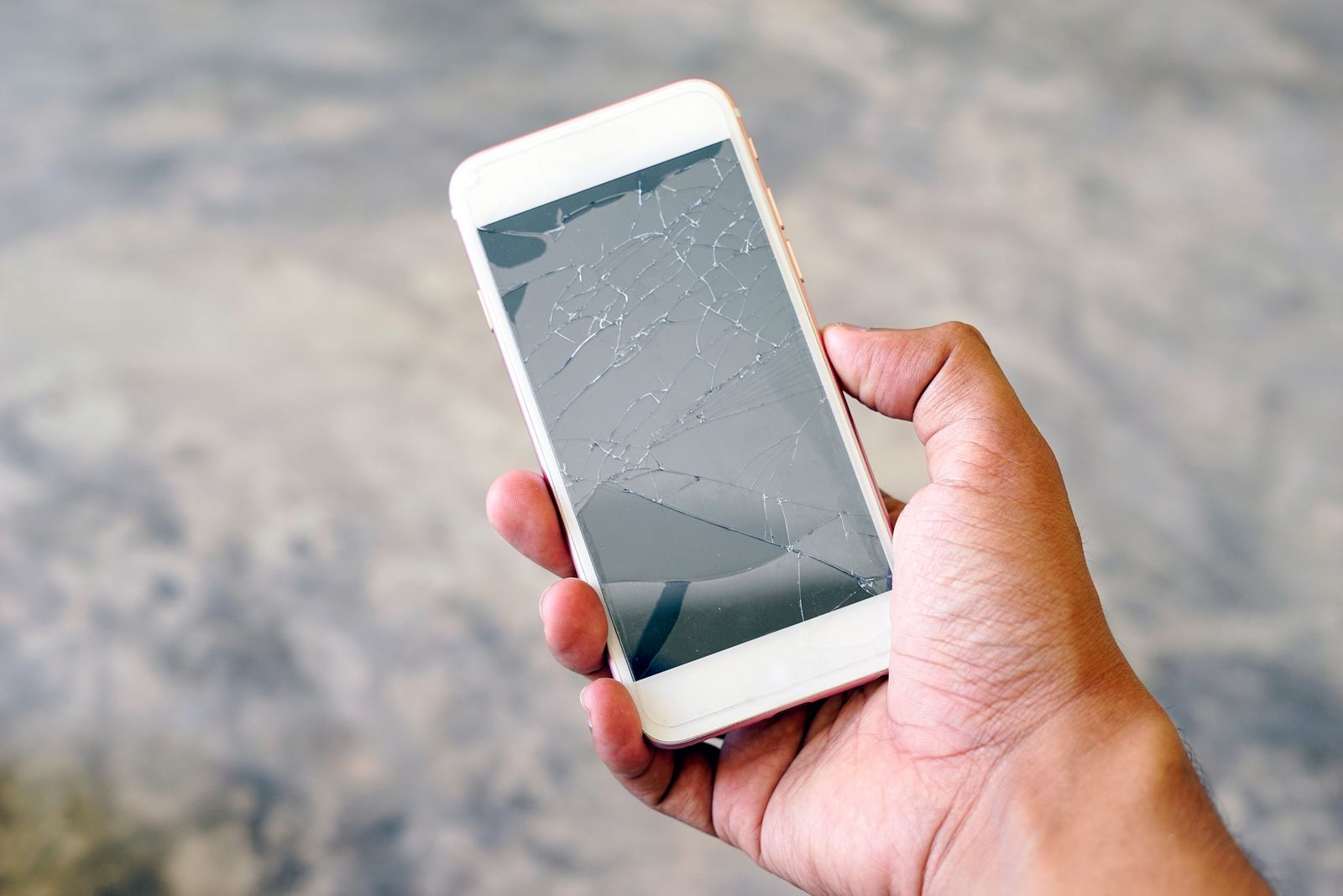 Close-Up Of Hand Holding Damaged Mobile Phone