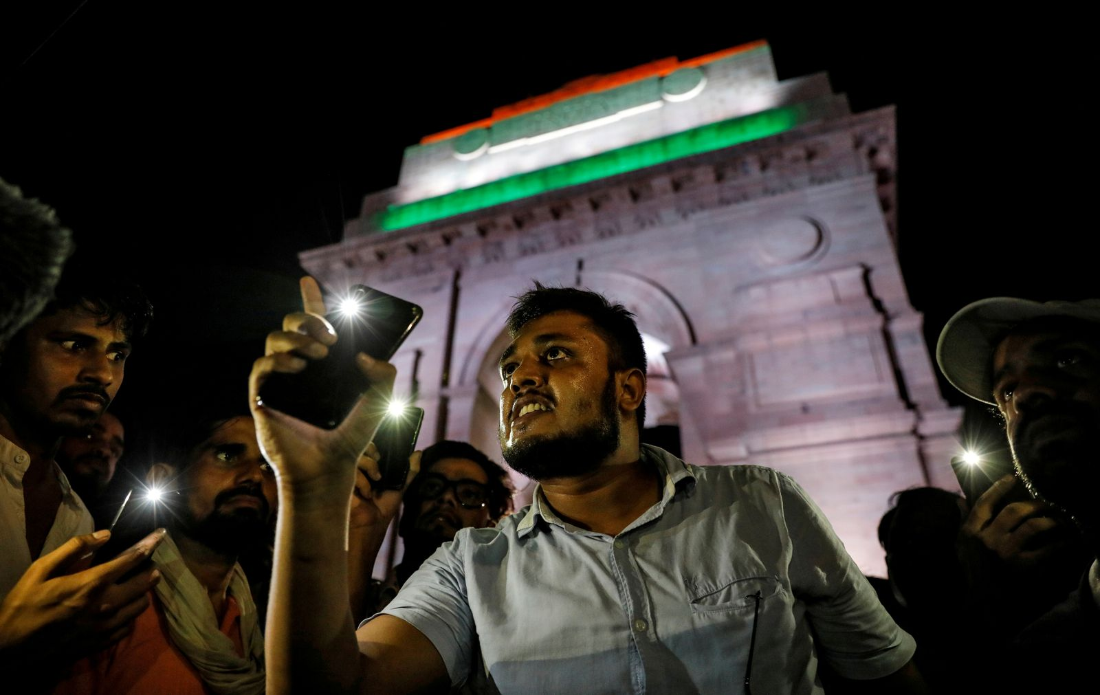 People hold their mobile phone torches as they take part in a protest demanding investigation in a highway collision in which a woman who is fighting a rape case against a legislator of the ruling BJP party was critically injured, in New Delhi