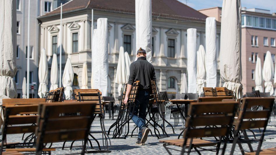Stühle eines Cafés in Augsburg werden für den Außenbereich aufgestellt