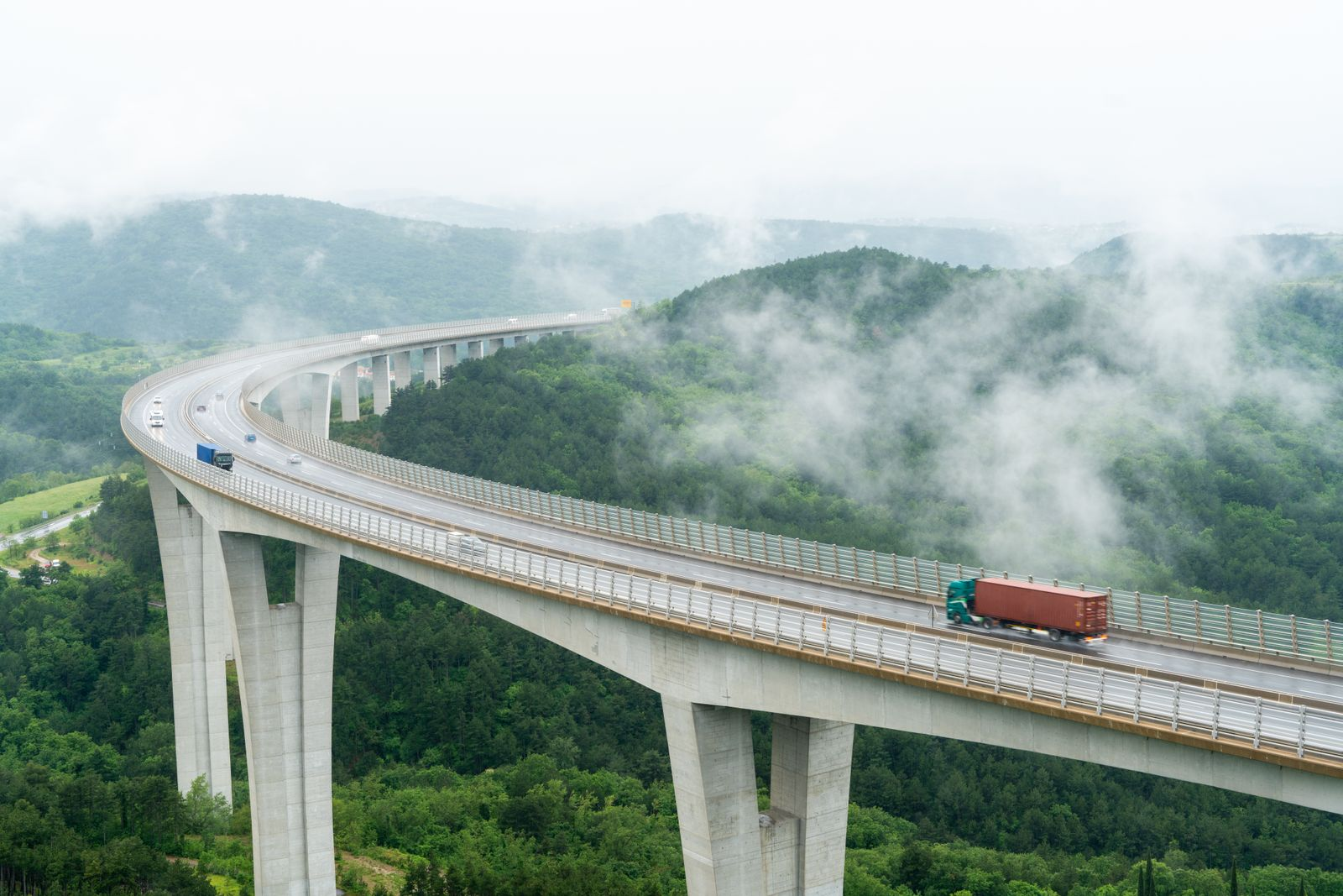 Aerial view of trucks on viaduct and hills in background in fog, Crni Kal, Littoral region, Slovenia