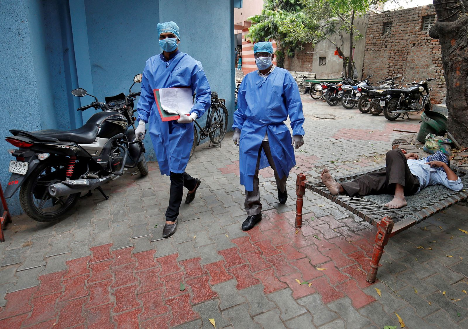 Police officers in protective suits arrive in a residential area to check on people under home quarantine in Ahmedabad
