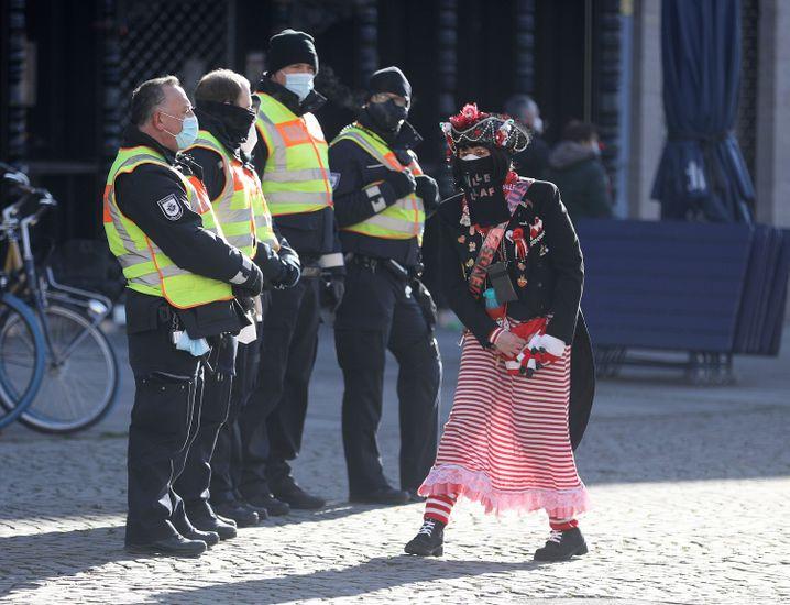 Tanzende Karnevalistin und Mitarbeiter des Kölner Ordnungsamts auf dem Alter Markt