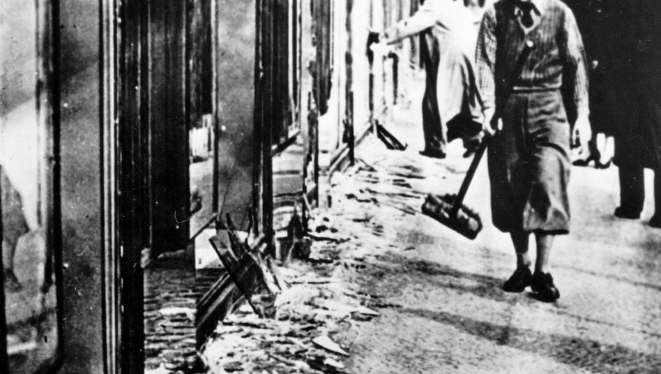 Der Tag nach dem Pogrom: Am Morgen des 10. November 1938 kehrt ein Mann die Scherben vor einem Geschäft zusammen