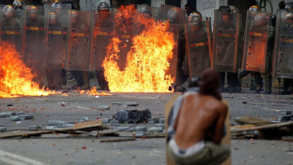 Ein Demonstrant steht Sicherheitskräften in Venezuela gegenüber