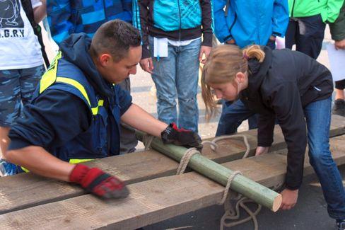 Eine Schülerin und ein Helfer des THW bauen eine provisorische Brücke aus Holzbohlen beim »Tag der Flüsse« 2016.