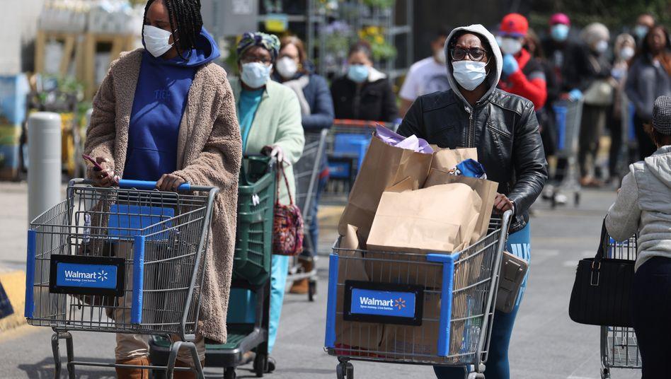 Walmart-Kunden mit Masken und Handschuhen stehen Schlange vor einer Filiale in New York