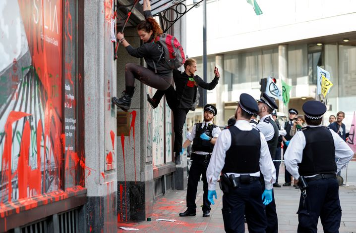 Extinction Rebellion protestors climb down from the awning of the Brazilian embassy in London.