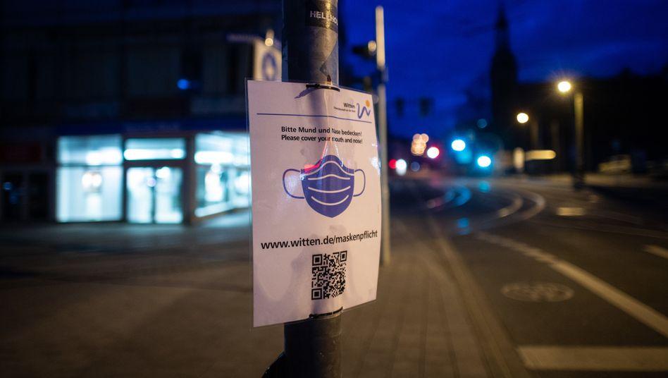 Hinweisschild auf die Maskenpflicht in einer leeren Fußgängerzone im nordrhein-westfälischen Witten
