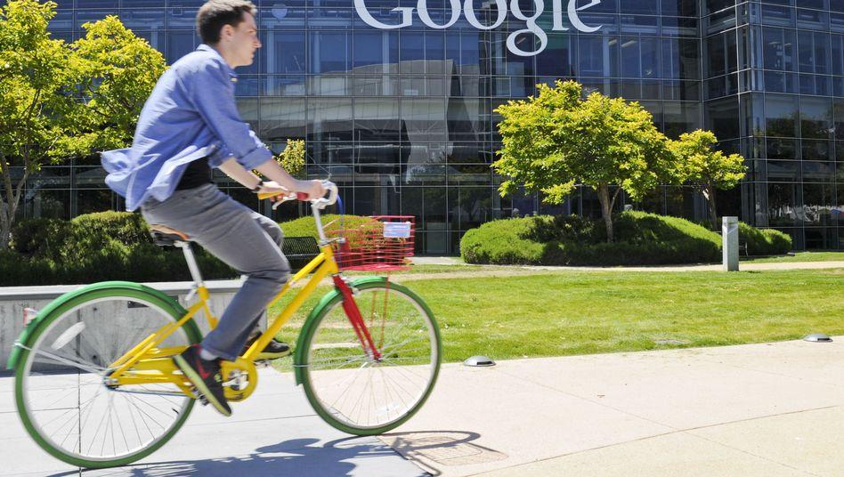 Fahrradfahrer vor dem Logo des Internetkonzerns Google im Silicon Valley