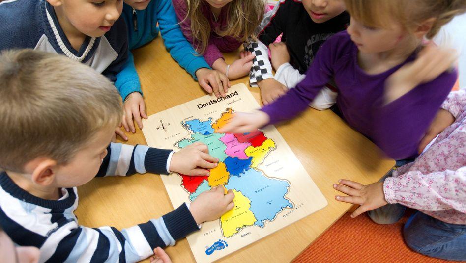 Gemeinsam zum Ziel: Gemeinsam lösen Kinder ein Puzzle mit einer Deutschlandkarte